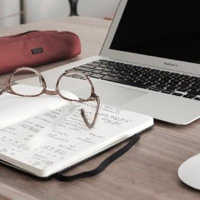 block notes in primo piano con occhiali appoggiati su scrivania con pc portatile