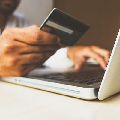 uomo con carta di credito intendo ad effettuare un acquisto online